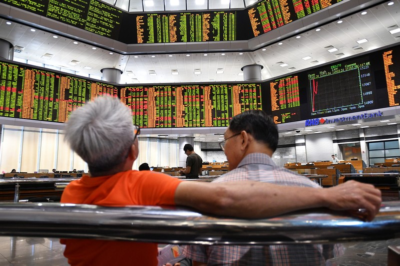 People look at trading boards at a private stock market gallery in Kuala Lumpur