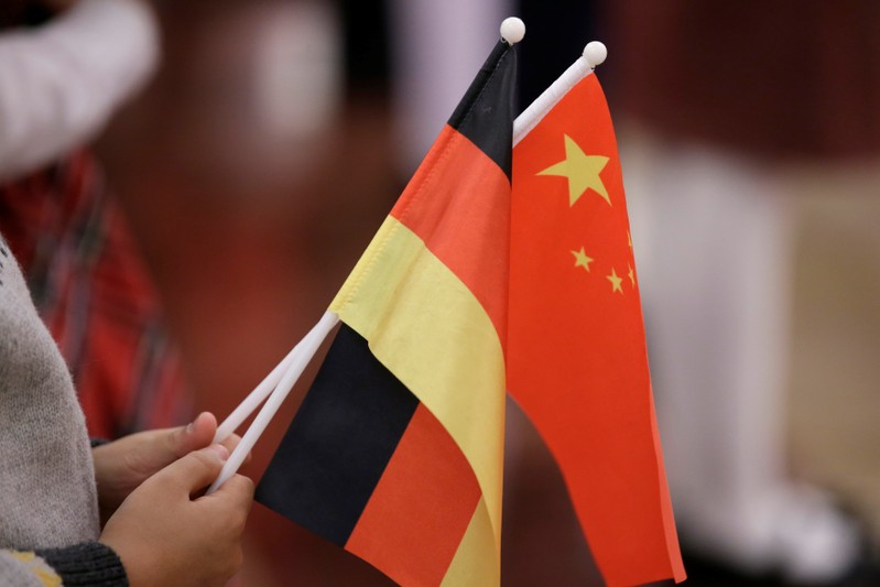 A student holds flags of China and Germany before a welcome ceremony in Beijing