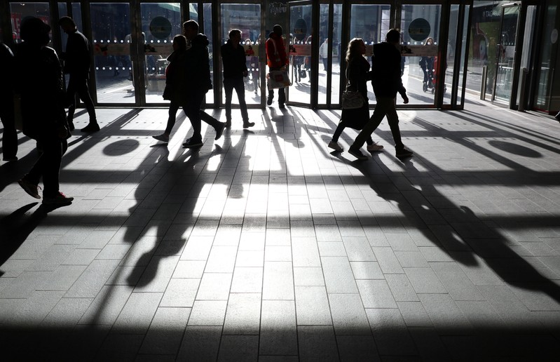People's shadows are seen as shoppers are silhouetted in the bright sunshine at the Westfield shopping centre, Stratford, London