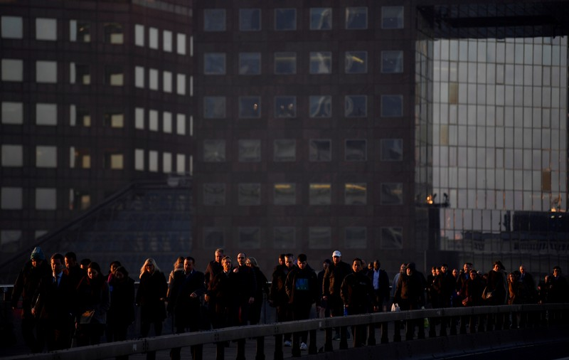 Workers cross London Bridge during the morning rush hour in the city of London, Britain