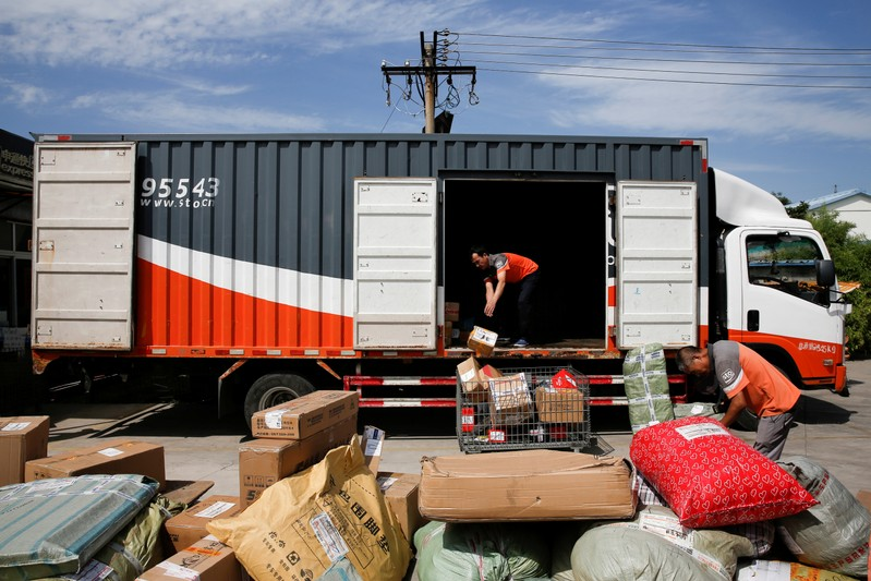 FILE PHOTO: Workers unload parcels from a truck at a distribution hub of the Chinese delivery company Shentong (STO) Express in Beijing