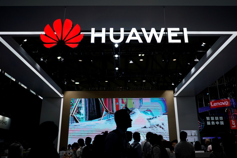 FILE PHOTO: People walk past a sign board of Huawei at CES (Consumer Electronics Show) Asia 2018 in Shanghai
