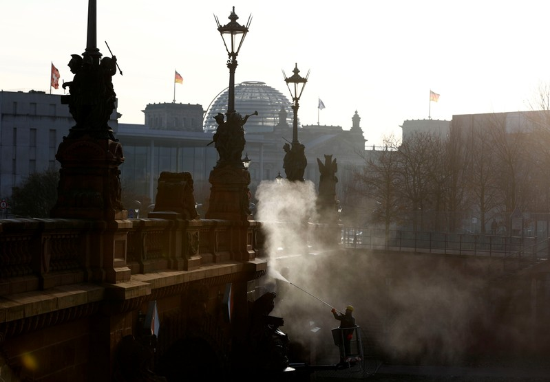 A worker cleans with hot steam the surface of Moltkebrueke Bridge near the Chancellery, in the early morning in Berlin