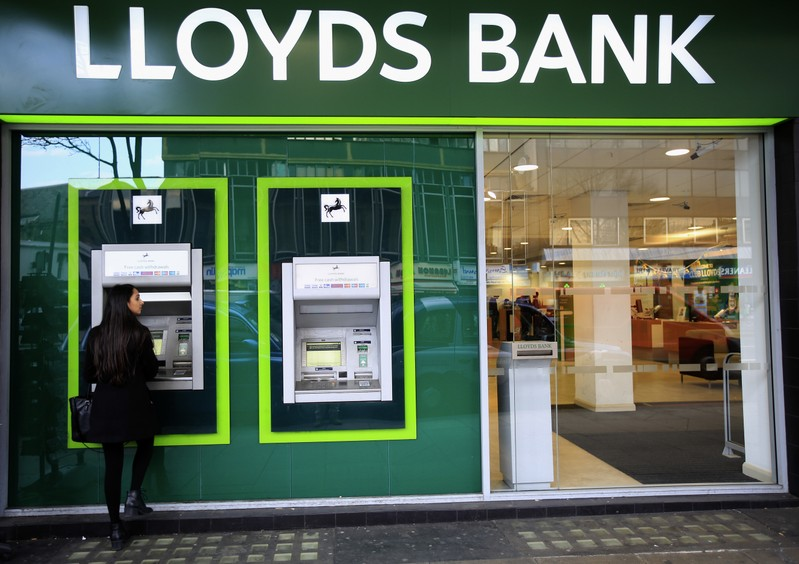 A woman uses a cash machine at a Lloyds Bank branch in central London