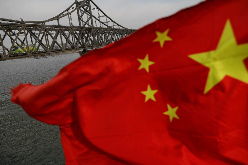 FILE PHOTO: A Chinese flag is seen in front of the Friendship bridge over the Yalu River connecting the North Korean town of Sinuiju and Dandong in China's Liaoning province