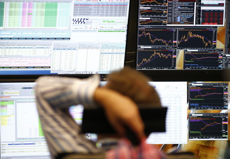 FILE PHOTO: A trader sits in front of the computer screens at his desk at the Frankfurt stock exchange