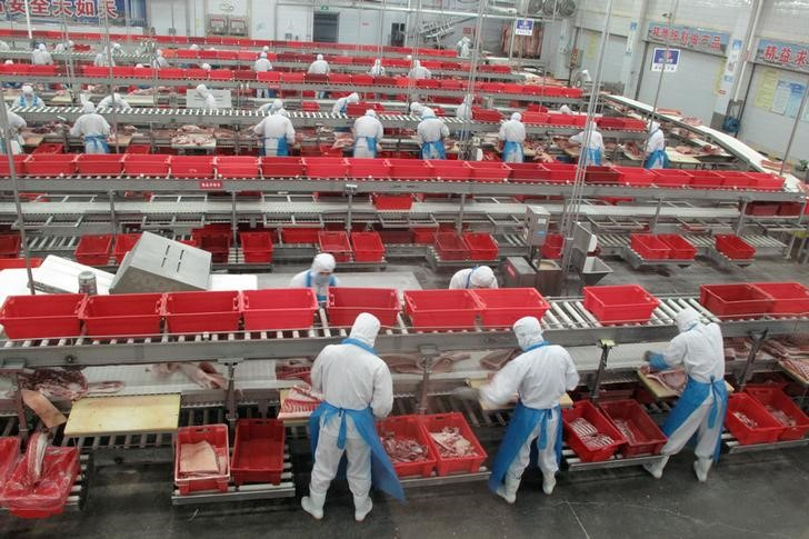 Workers sort cuts of fresh pork in a processing plant of pork producer WH Group in Zhengzhou