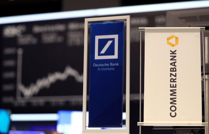 FILE PHOTO: Banners of Deutsche Bank and Commerzbank are pictured in front of the German share price index, DAX in Frankfurt