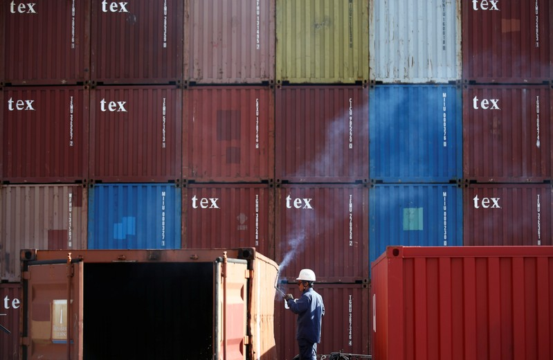 A man repairs a container at an industrial port in Tokyo