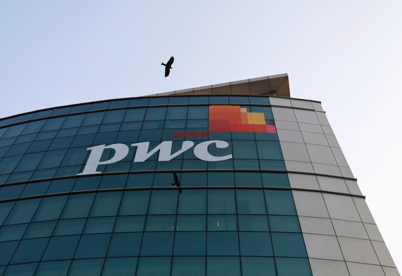 A bird flies past the logo of Price Waterhouse installed on the facade of its office in Mumbai