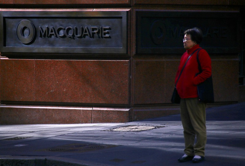 A pedestrian stands near the logo of Australia's biggest investment bank Macquarie Group Ltd which adorns a wall on the outside of their Sydney office headquarters in central Sydney, Australia