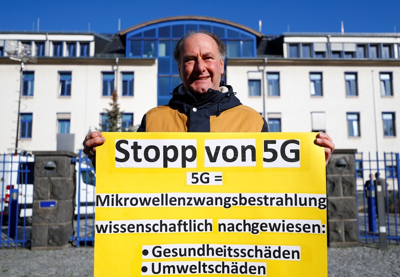 A protestors holds a placard against 5G mobile communication standards as he stands in front of the head quarters of Germany's Federal Network Agency (Bundesnetzagentur) prior to the auction of spectrum for 5G services at the Bundesnetzagentur in Mai