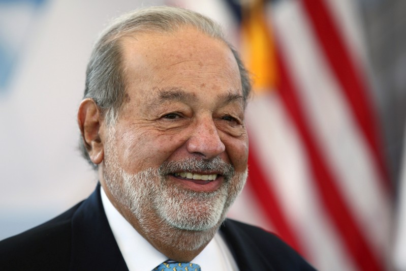 FILE PHOTO: Mexican billionaire Carlos Slim smiles as he attends a ceremony to place the first stone of the new U.S. Embassy in Mexico City