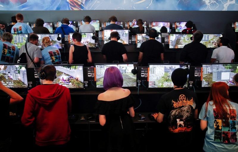 FILE PHOTO: Gamers play video games during the opening of the world's largest computer games fair Gamescom in Cologne