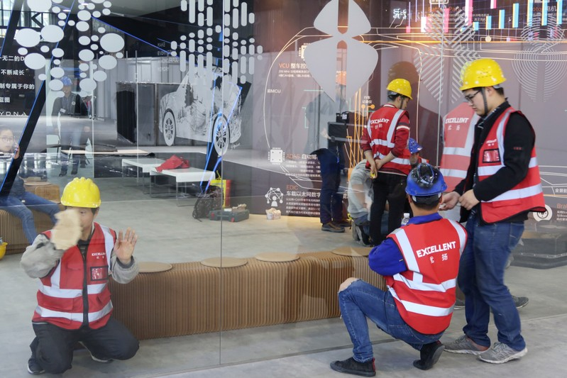 Workers set up the display stand for Chinese EV startup Singulato Motors in preparation for the upcoming auto show in Shanghai