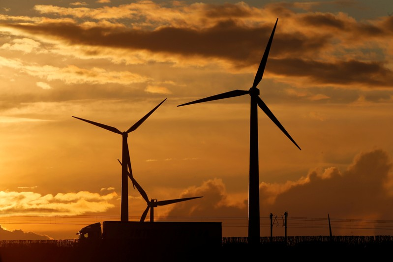 FILE PHOTO: A truck drives in front of power-generating windmill turbines on the Paris-Lille highway during sunset in Wancourt