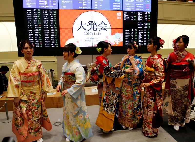 Women, dressed in ceremonial kimonos, chat in front of an electronic board showing stock prices after the New Year opening ceremony at the Tokyo Stock Exchange (TSE), held to wish for the success of Japan's stock market, in Tokyo