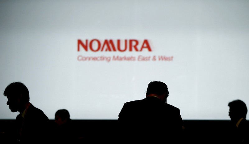 FILE PHOTO:  File photo of investors standing in front of a screen showing the logo of Nomura Holdings in Tokyo