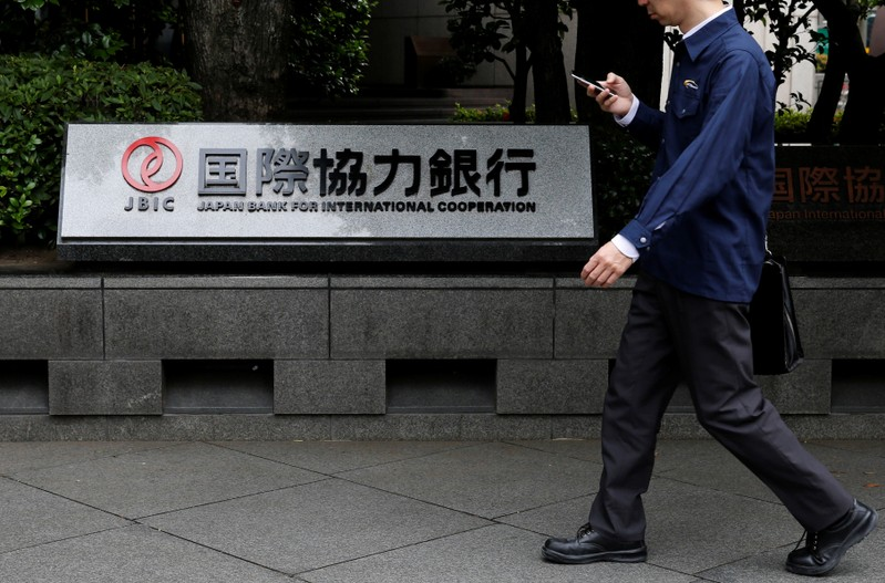 Man walks past a sign of Japan Bank for International Cooperation (JBIC) at it's headquarters in Tokyo