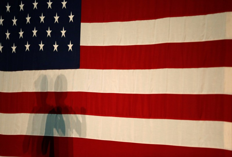 The shadow of Democratic 2020 U.S. presidential candidate and U.S. Senator Elizabeth Warren is projected onto an American flag  during a townhall event in Columbus, Ohio
