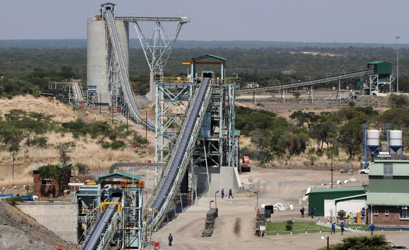 FILE PHOTO: Employees walk under a concentrator at Ngezi platinum processing plant near Harare