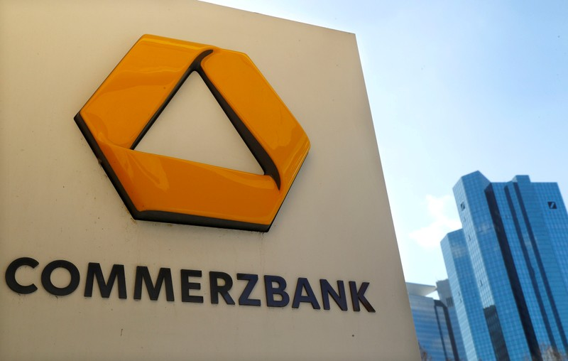 FILE PHOTO: FILE PHOTO: A sign for an ATM of Commerzbank is seen next to the headquarters of Deutsche Bank (R) in Frankfurt