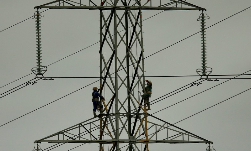 Workers paint an electricity pylon near Lymm, northern England