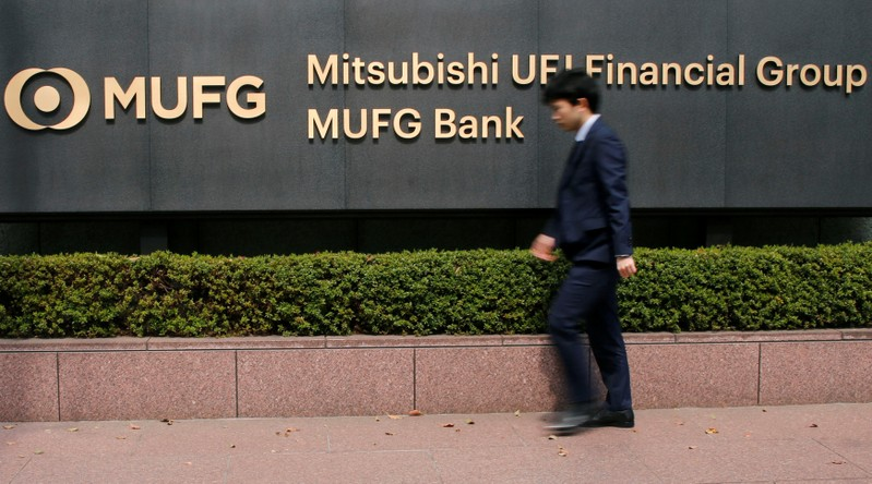 A man walks past a signboard of Mitsubishi UFJ Financial Group and MUFG Bank at its headquarters in Tokyo