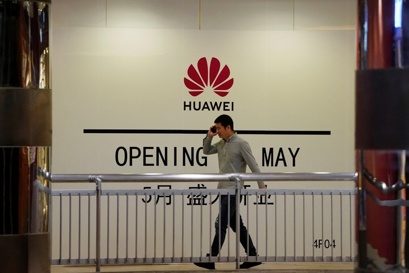 Man using his mobile phone walks past a yet-to-open Huawei store inside a shopping mall in Shanghai