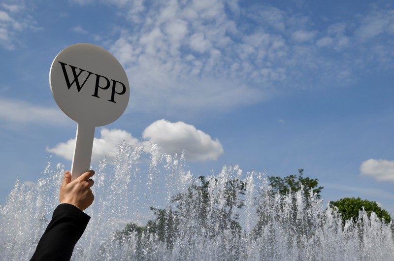 FILE PHOTO: An usher holds a baton to guide attendees towards the AGM of advertising agency WPP in London, Britain