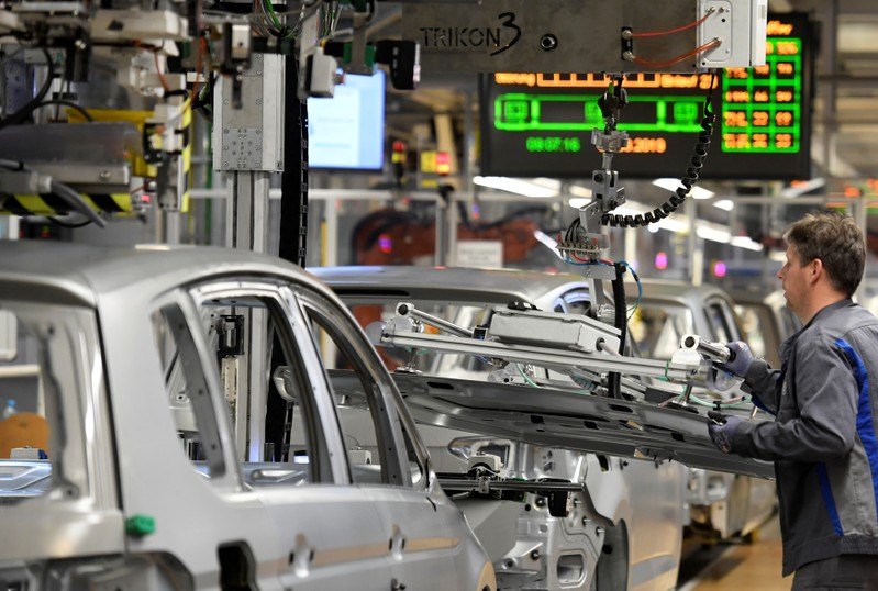An employee moves car components in a production line at the Volkswagen plant in Wolfsburg