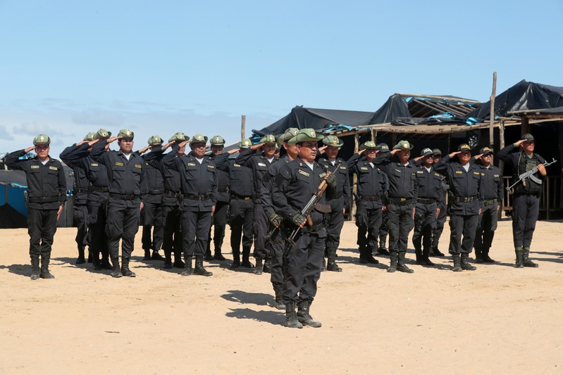 Peruvian police stand guard during Peru's President Martin Vizcarra visit to an illegal gold mining camp in Madre de Dios
