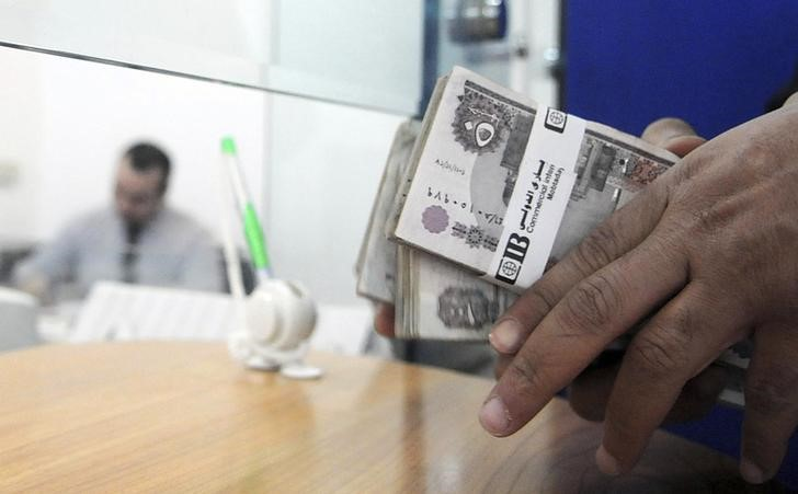 A customer counts his money in a bank in Cairo