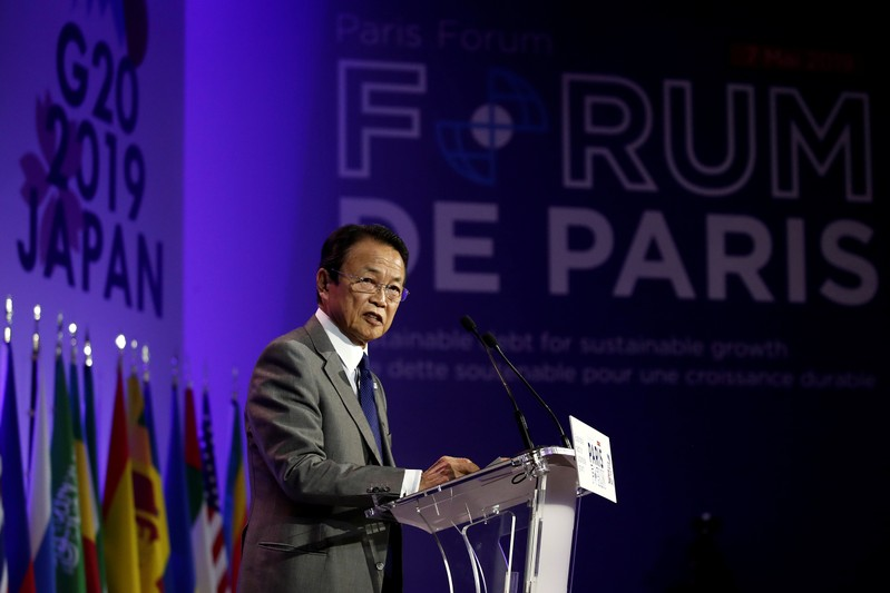 Japanese Finance Minister Taro Aso delivers a speech during a high-level forum on debt at the Finance Ministry in Paris