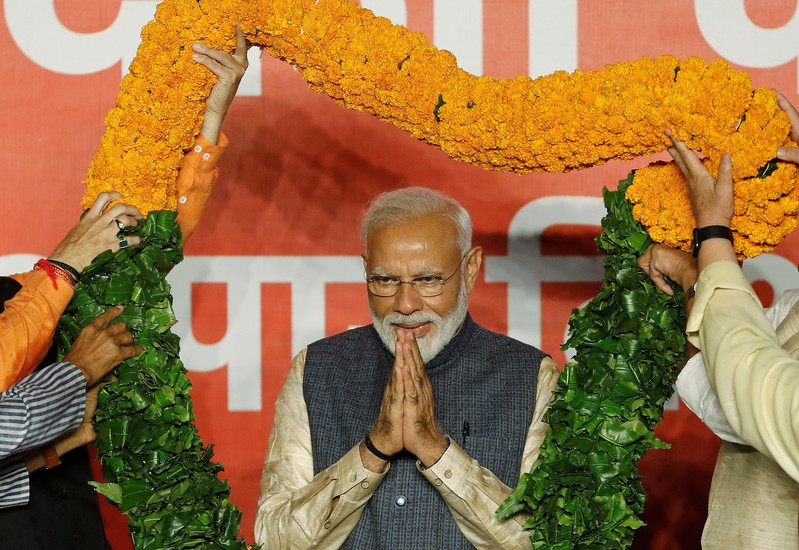 Indian Prime Minister Narendra Modi gestures as he is presented with a garland by Bharatiya Janata Party (BJP) leaders after the election results in New Delhi