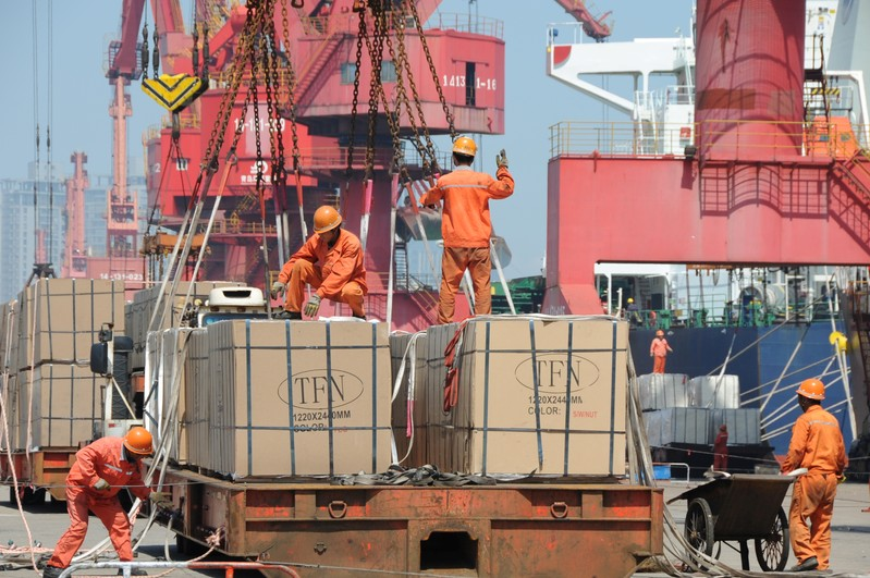 Workers load goods for export onto a crane at a port in Lianyungang