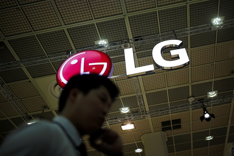 FILE PHOTO: A man talking on his phone walks past the logo of LG Electronics during Korea Electronics Show 2016 in Seoul