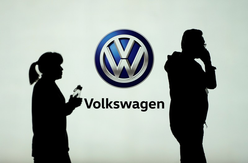 People pass in front of a Volkswagen logo ahead of the Shanghai Auto Show