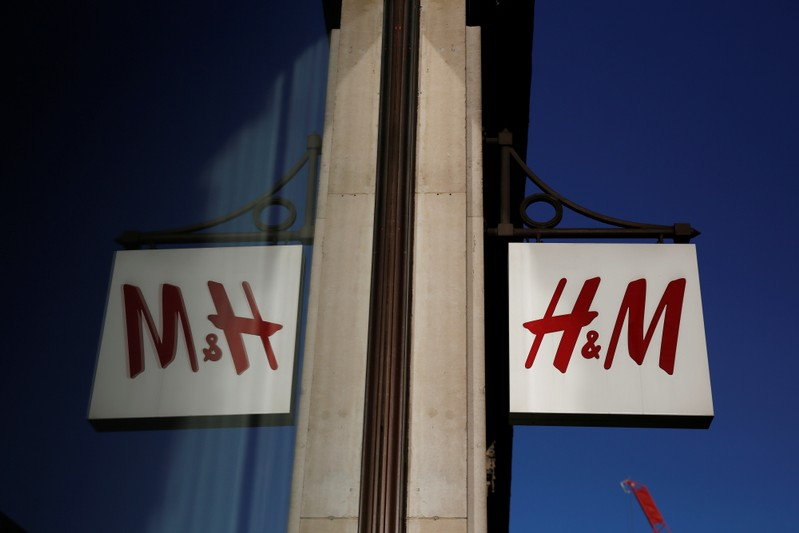 A logo is reflected in the window as it hangs outside the H&M store on Oxford Street in London