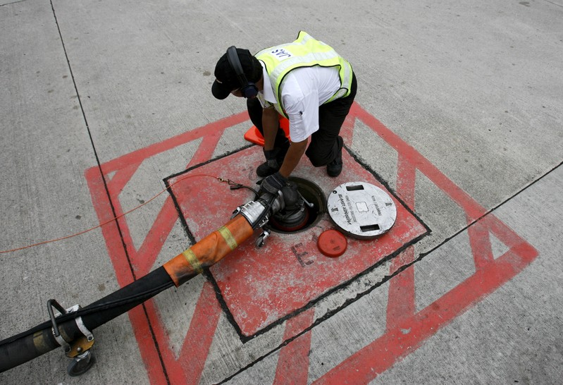File photo of a technician attaching a jet fuel supply pipe to outlet in tarmac at Changi airport in Singapore