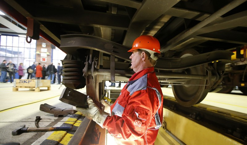 Deutsche Bahn technician fits a new noise reduced brake pad on goods wagon at railway repair center in Berlin