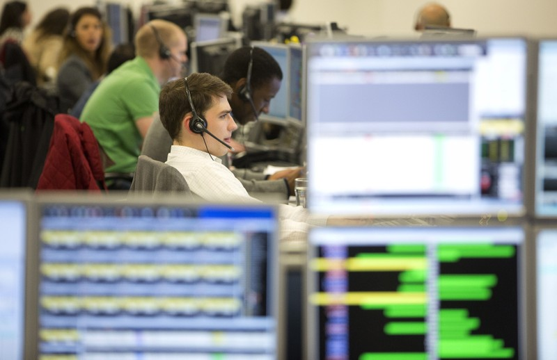Traders take telephone calls on the IG Group trading floor in London