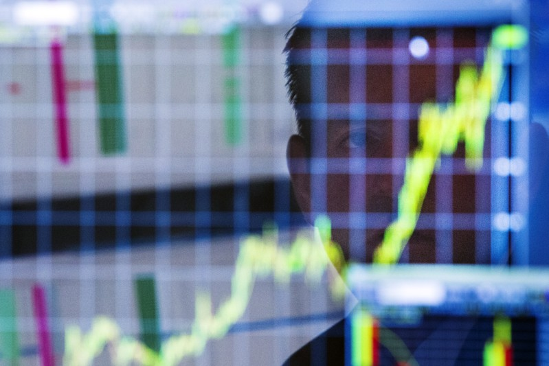 A trader looks up at a chart on his computer screen while working on the floor of the New York Stock Exchange in New York