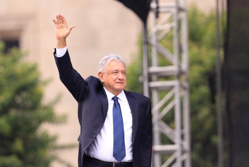 Mexico's President Andres Manuel Lopez Obrador waves on the first anniversary of his presidential election victory at Zocalo Square in Mexico City
