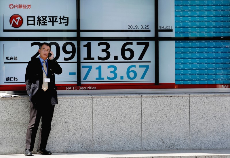 A man stands in front of an electronic board showing the Nikkei stock index outside a brokerage in Tokyo