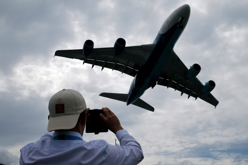 FILE PHOTO: A visitor takes a picture of an Airbus A380 as it lands after an air display at the 53rd International Paris Air Show at Le Bourget Airport near Paris