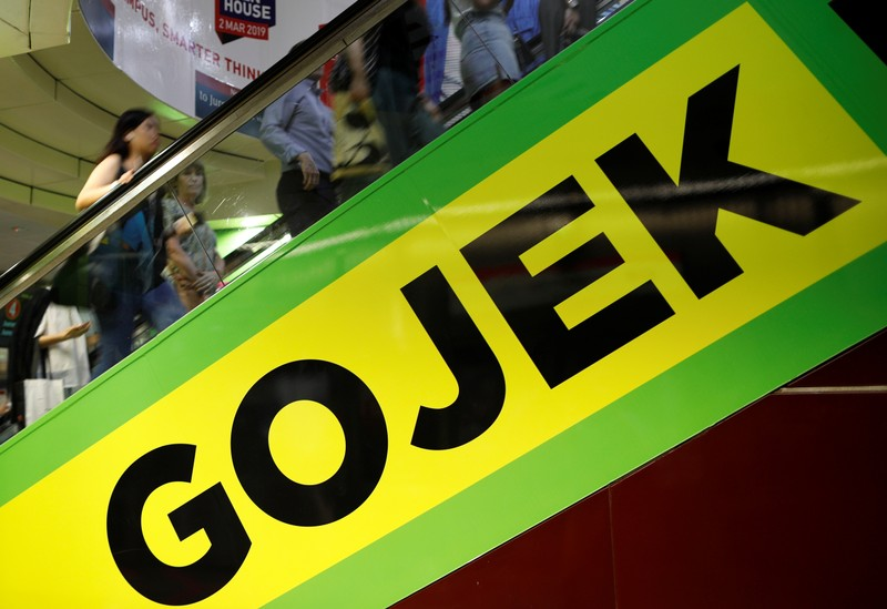 Commuters pass by a Gojek advertisement in Singapore