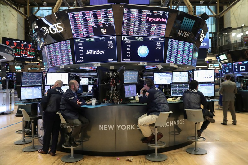 Traders look at price monitors as they work on the floor at the New York Stock Exchange (NYSE) in New York City