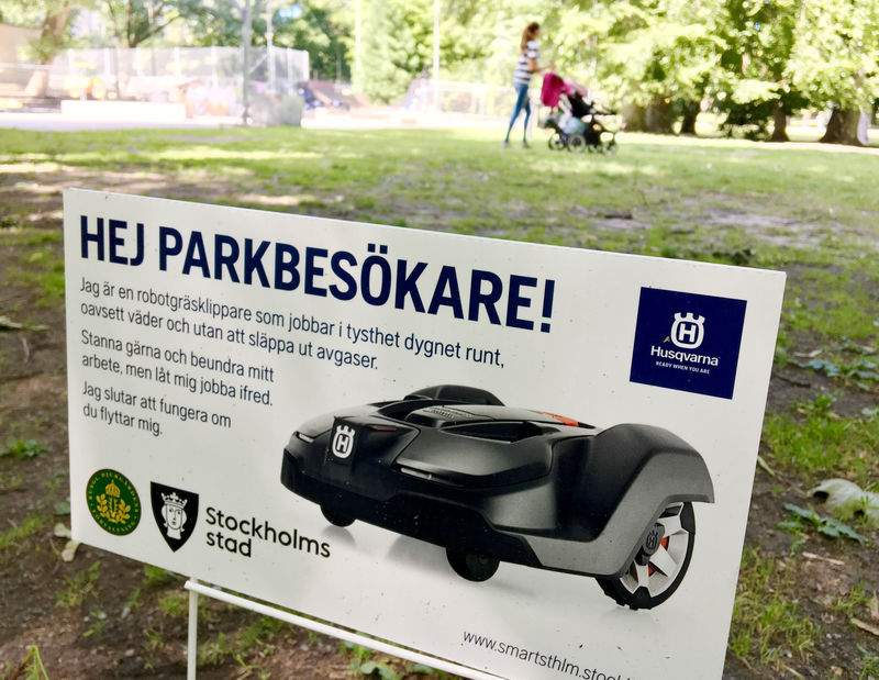 FILE PHOTO:  A sign alerts visitors about a presence of Husqvarna robotic lawn mower at work in the Humlegarden park in Stockholm