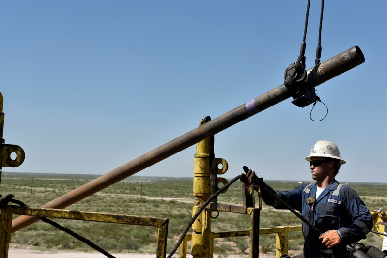 A drilling crew member raises drill pipe onto the drilling rig floor on an oil rig in the Permian Basin near Wink